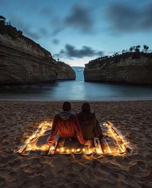 Couple Enjoying Evening Sunset, Sitting On Sand,Watching Blue Water