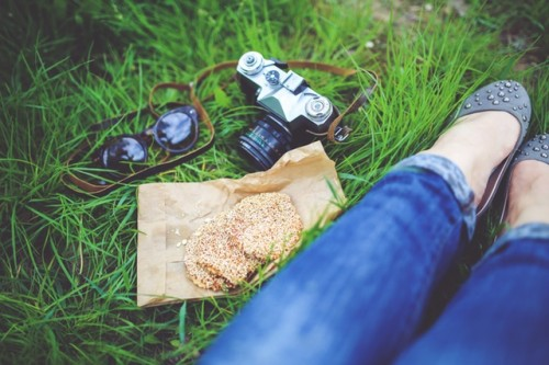 Girl resting on grass with cookies and camera