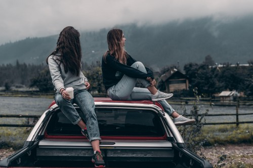 Two Women Sitting on vehicle roofs - Brosteni, Romania