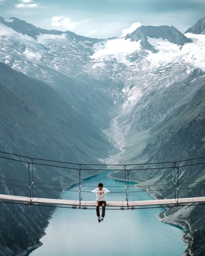Sitting on a suspension bridge in the Austrian Alps