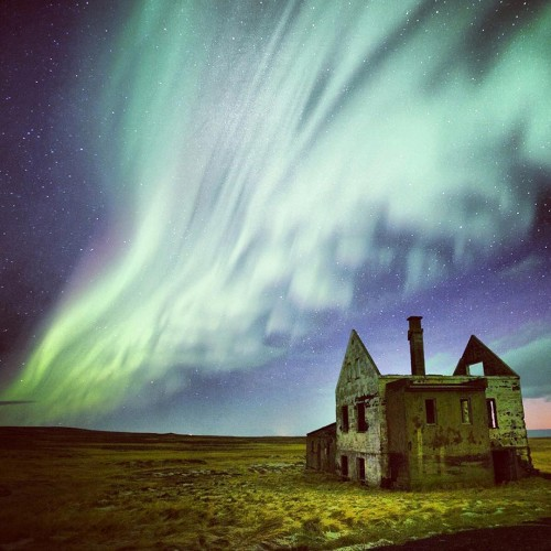The Aurora Borealis flows like a river over an abandoned building on the  Snaefellsnes Peninsula in Iceland.
