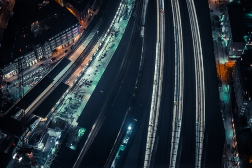 Aerial Train Station During Night Hours,bird's eye view  buildings, city  lights  nightscape, railway lines  road, train station