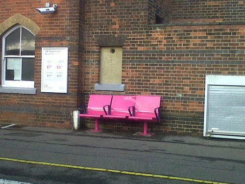 Colorful seats in an otherwise deserted and grayish United Kingdom station. London, bench, pink, old building