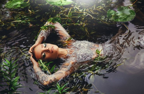 Woman-in-long-sleeved-dress-surrounded-by-water-plants