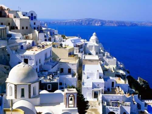 Santorini: Village of White and Blue, Santorini in the Greek Islands ... The houses and building structures are predominantly white, some with blue dome roofs accented by beautiful blue skies and overlooking the blue sea