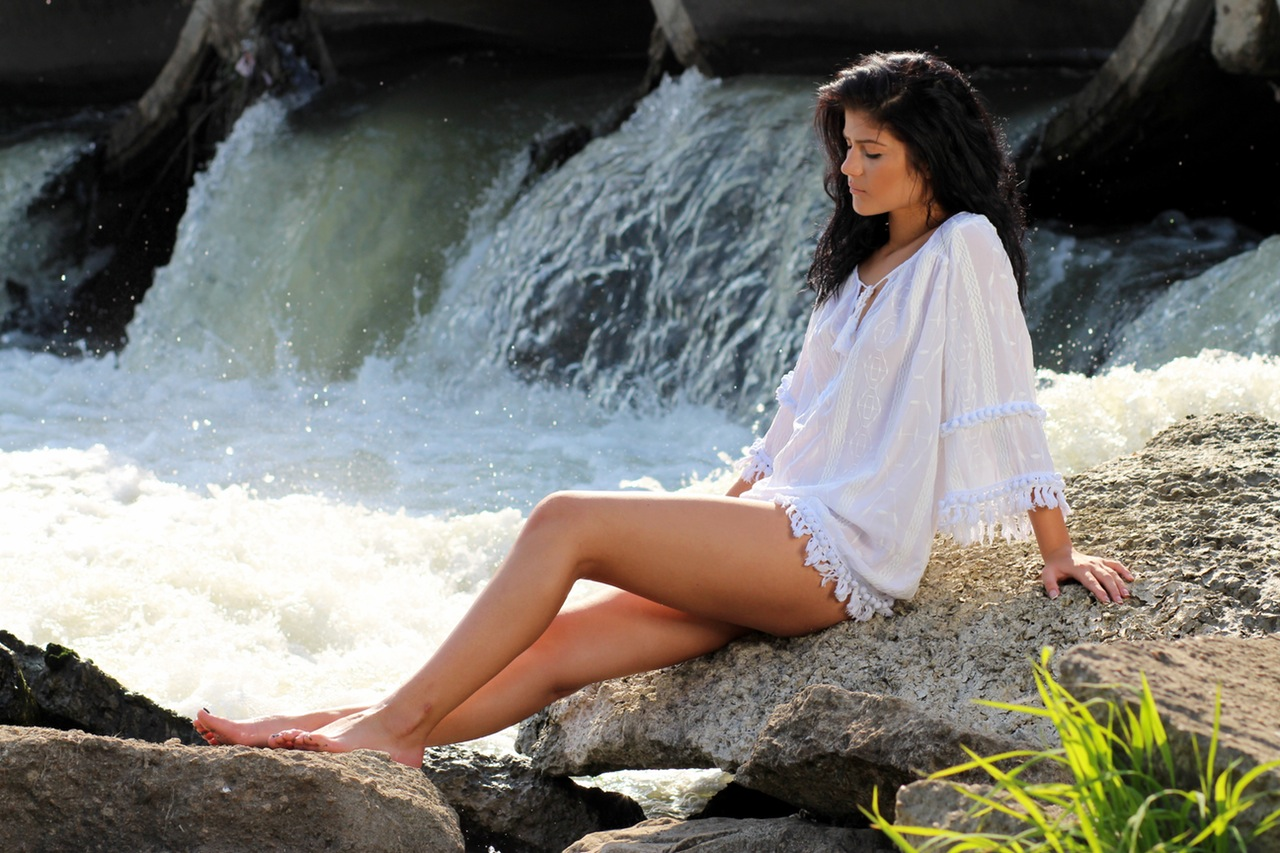 Young Caucasian Woman Sitting On The Rock And Enjoying